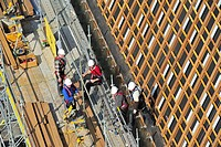 Construction workers protected by safety harnesses and hard hats on scaffold working on roof, Ghent, Belgium