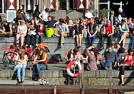People enjoying the first spring sun by the waterside along the Graslei at Ghent, Belgium