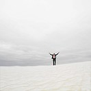 Businessman in the desert with his arms outstretched