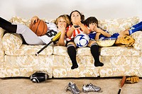 Group of children in sports gear watching television on the sofa