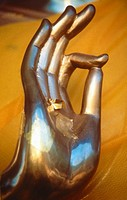 brass Buddha hand with gold leaf applied to palm Thailand  Vitarka mudra intellectual argument, wheel of law