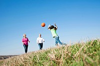Girl playing ball with her grandparents on a meadow