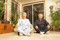 Senior Asian couple sitting cross_legged on the floor