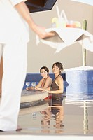 Two Hispanic women with drinks in a hotel pool