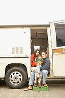 Family sitting in doorway to recreational vehicle