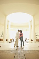 Couple kissing in hotel lobby