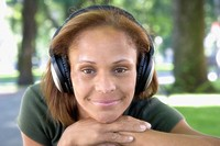 Close up of African woman wearing headphones in park