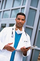 African male doctor holding chart outdoors