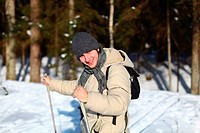 Closeup of young man cross_country skiing on a sunny winter day through the forest