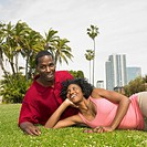 African couple laying in grass smiling
