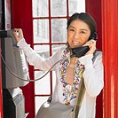 Asian woman using public telephone box in London