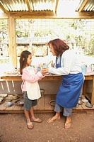 Hispanic woman and girl in pottery shop