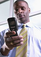 Low angle view of African businessman using cell phone