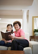 Asian grandmother and granddaughter reading