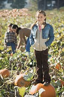 Girl standing on pumpkin in pumpkin patch