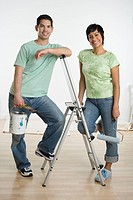 Portrait of Hispanic couple holding painting supplies