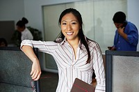 Asian businesswoman leaning on cubicle wall