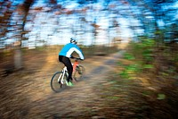 Bicycle riding in a city park on a lovely autumn/fall day motion blur is used to convey movement