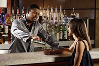 African male bartender pouring drink