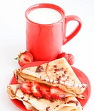sweet meal with cup of milk and cakes and chocholate and strawberries