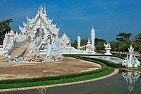 Fantastic snow_white palace. It is built in style of new Thai architecture. It is superb reflected in a pond