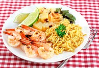 Delicious barbecued shrimp, peppers, and pineapple on a plate with lime and rice curry.