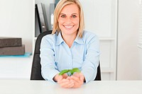 Woman holding a little plant into camera in her office
