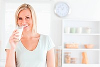 Woman drinking milk looks into camera in kitchen