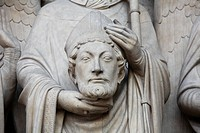 Medieval statue of Saint Denis holding his head at the entrance portal of the Notre Dame cathedral in Paris, France
