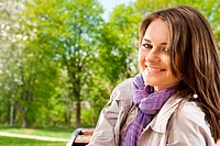 Attractive young girl smiling in park. Face close_up