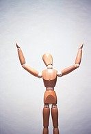 Wooden artists mannequin with hands in air, concept photography