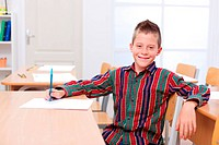 Confident boy in empty classroom, sitting alone at table