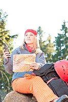 Active young woman backpack search navigation map rock climbing