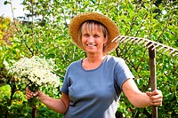 Portrait of happy mature woman holding flowers and rake in the garden.