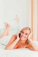 Happy woman answering the phone while lying on her bed