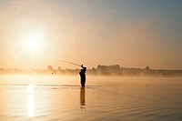 Fisherman´s silhouette fishing at sunrise in lake