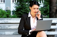 Business woman sitting on bench in park and working on laptop
