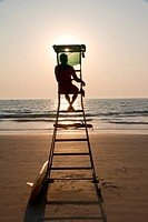 Lifeguard silhouette overlooking tropical beach, Goa India