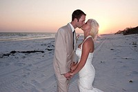 horizontal photograph of a bride and groom on the beach at sunset