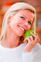 casual woman smiling with an apple at home