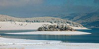 Unfrozen lake in the winter forests of Rhodopes, Bulgaria. Blue cold water and snow island