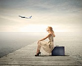 Beautiful woman sitting on a suitcase with airplane in the background