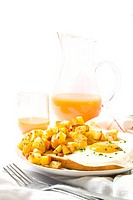 Breakfast still with healthy orange juice in the background. Fried egg with yolk intact on a toast bread and fried potatoes on a white plate. White co...