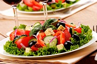 Greek salad and glasses of red wine on the oak table