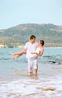 outdoor portrait of young romantic couple in white cotton clothes on beach of Phuket island, Thailand. guy is holding girl on hands