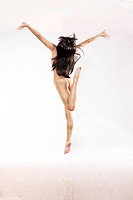 Naked girl jumps into air on whtie studio background