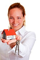 Realtor woman offering house keys and small house
