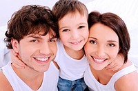 Funny smiling faces of young family looking at camera