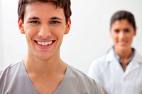 Portrait of happy male doctor standing with female doctor standing in background