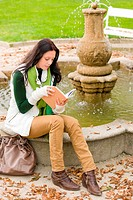 Autumn park young woman reading book sitting on fountain